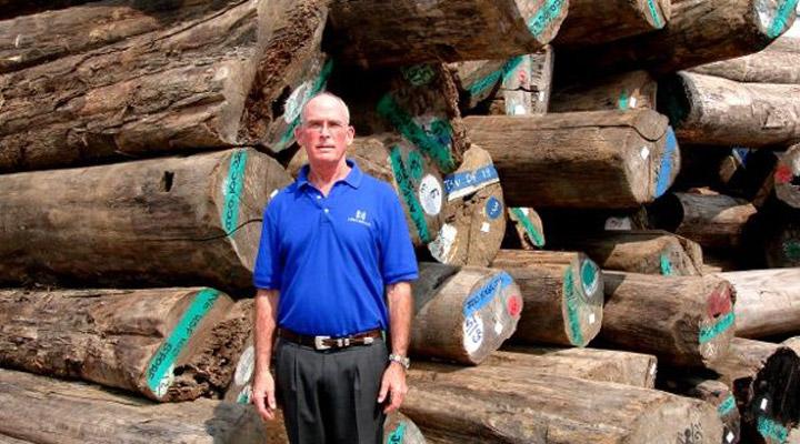 gib mcilvain in front of teak logs