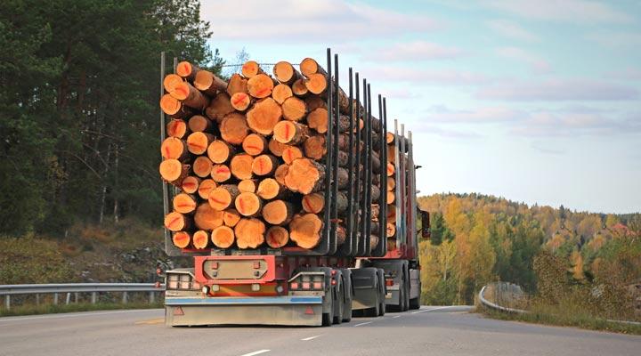 log truck driving down highway road